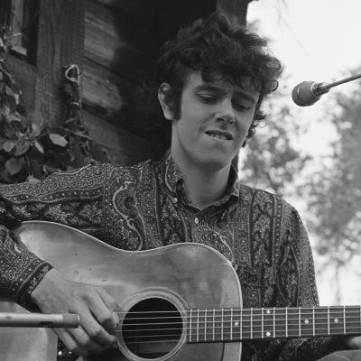 Folklaulaja Donovan soittaa kitaraa Ohimennen-ohjelmassa saunan portailla.