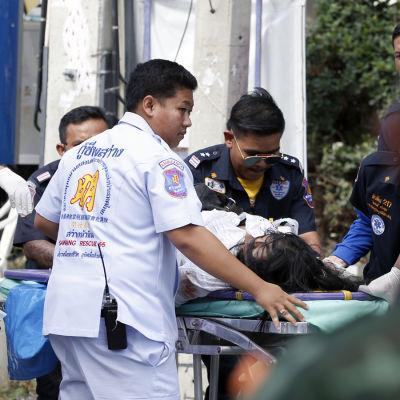 Medicinsk personal hjälper och flyttar på en skadad som ligger på en bår efter explosioner i Hua Hin, thailand.