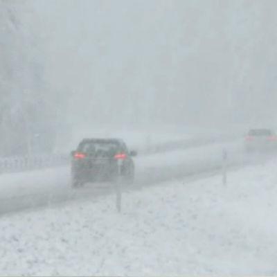 Bilar i snöfall på väg.