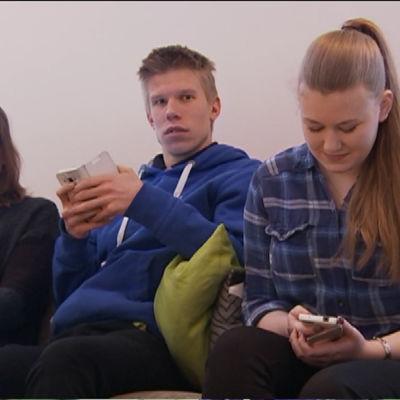 Två flickor och en pojke sitter ien  soffa i aulan i Sibbo gymnasium