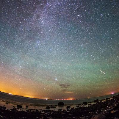 Stjärnfall från perseiderna på en gul, lila, grön och blåfärgad himmel över den tyska ön Fehmarn i augusti 2015.