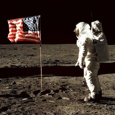 Vi är uppe i rymden. En man är klädd i en helvit rymddräkt. Han vandrar på en plan sandyta. I mitten på planen står den amerikanska flaggan. På sandytan syns märken av mannens skor. Bakgrunden är svart.