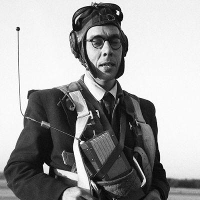 Usko Santavuori laskuvarjohyppääjän varusteissa mikrofoni rintaan kiinnitettynä (1950).