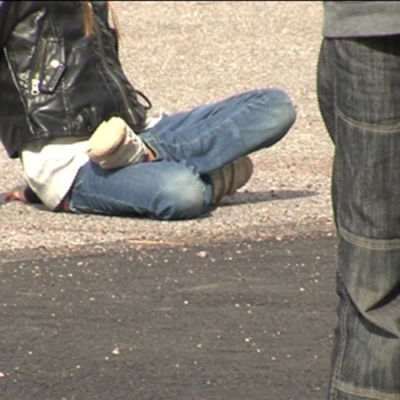 Ungdom sitter ute på marken medan en annan står bredvid.