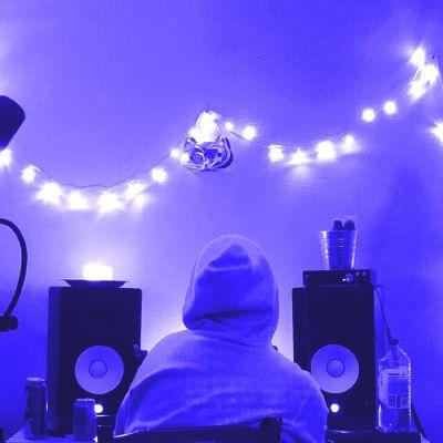 Huppupäinen hahmo istuu kahden kaiuttimen välissä tuottajapöydän ääressä, seinällä on valosarjoja. Kuvan sävy on sininen.
