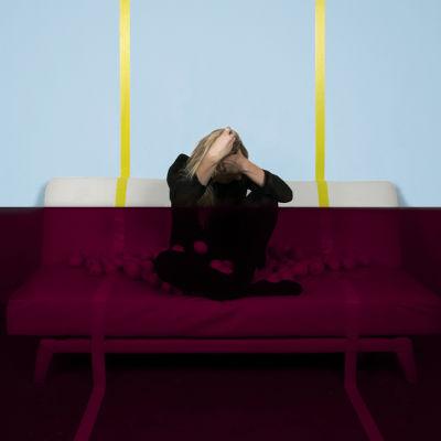 Verona-nimisen artistin promokuva, jossa hän istuu sohvalla pää painuksissa käsissä. Taustaseinä on alapuolelta tumma ja yläpuolelta kirkas.