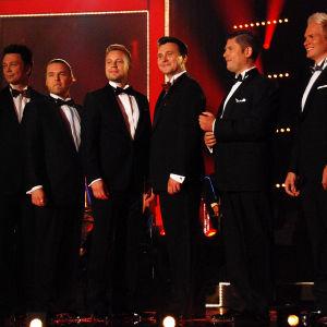 Miehet rivissä lavalla