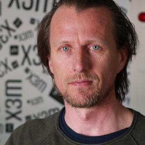 En man med kort skägg och grön tröja. Står framför en vägg där det står X3M.