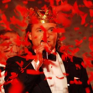 mies laulaa konfettisateessa