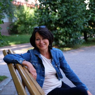 Monica Groop sitter på en parkbänk.