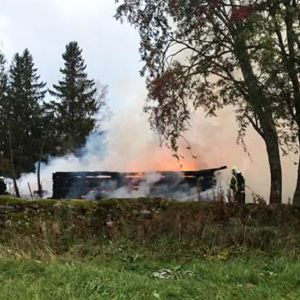 Rykande ruiner av Kiihtelysvaara träkyrka som totalförstördes i en brand.