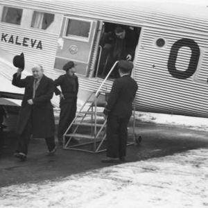"""Aero Oy:n Junkers Ju 52/3m """"Kalevan"""" (OH-ALL) matkustajia Helsingin lentoasemalla. Vasemmalla ylhäällä koneen siiven päälle kiivennyt starttipäällikkö, joka keskustelee ohjaamossa olevien lentäjien kanssa."""