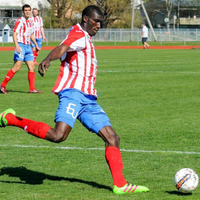 Alieu Ceesay sparkar bollen på gräsplan.