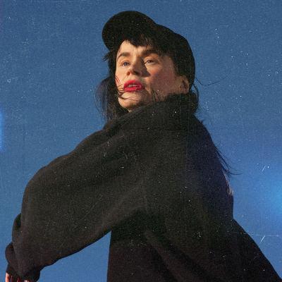 Artisti Sonja Inari sinistä taustaa vasten