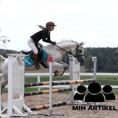 """En kvinna hoppar med en häst över ett hinder. På bilden finns en logotyp där det står """"min artikel""""."""