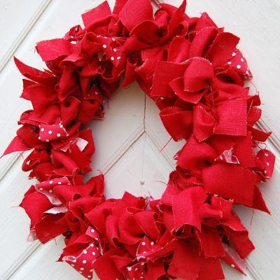 En röd julkrans av tyg som hänger på en vit ytterdörr.