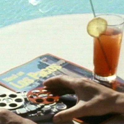 Pöydällä nauhuri, matkaesite ja juoma.