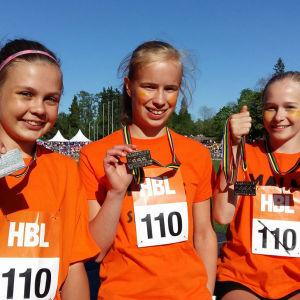 Tre flickor från Malms skola presenterar sina silvermedaljer efter lopp på Stafettkarnevalen.