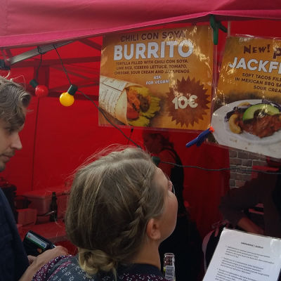 Två personer står framför ett gatukök som säljer tex-mex.