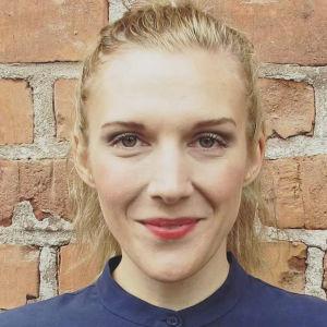 porträttbild av kvinna mot tegelvägg