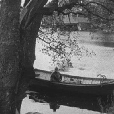Kalastaja liukuu veneellä rannan tuntumassa.