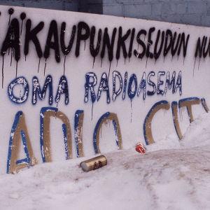 Radio Cityn pahvinen mainoskyltti Lepakkoluolan ulkopuolella.