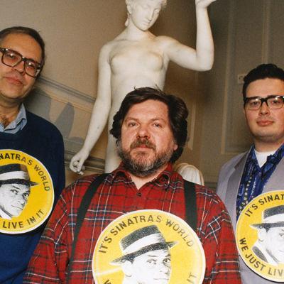 Frankien maailma -maratonlähetyksen tekijät Peter von Bagh, Juhani Similä ja Pekka Laine poseeraavat Ateneumin aulassa valtavat Sinatra-napit rinnassaan.