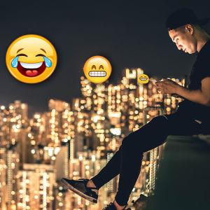 Man sitter och skriver emoijer på sin mobiltelefon.