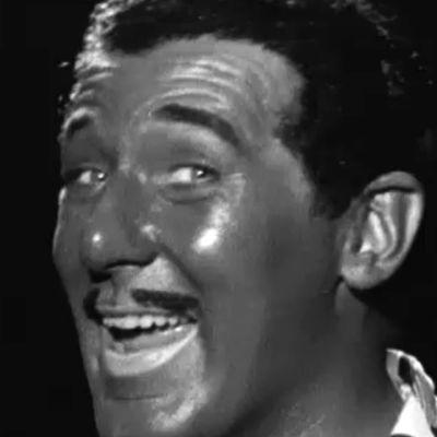 Näyttelijä Börje Lampenius laulaa viihdeohjelmassa mustaihoiseksi naamioituna (blackface).