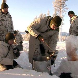 Varusmiehet ruokailevat talvisessa metsässä.