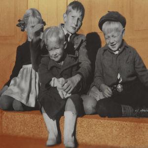 Barn som sitter i solen och kisar med ögonen.