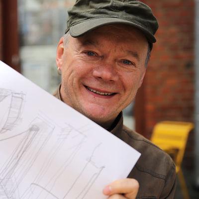 Lippalakkipäinen, naurava mies esittelee piirustusta lähikuvassa
