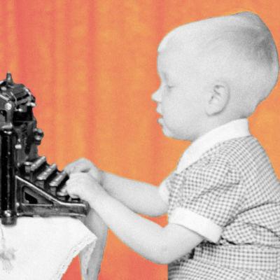 En liten pojke skriver med skrivmaskin