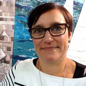 En kvinna med mörkt kort hår och svarta glasögon ler mot kameran.