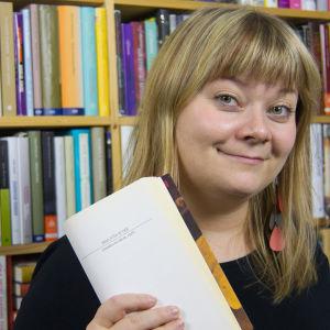 Kirjainten virrassa kirjabloggari Hanna kirjojen edessä kirja kädessään
