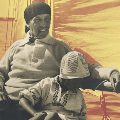 En man och ett barn i en segelbåt. Mannen har en pipa i munnen.