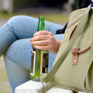En person sitter på en bänk med en ryggsäck och vinflaska bredvid sig.