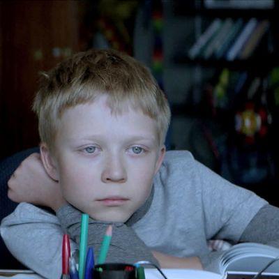 Koulupoika Aljosha (Matvei Novikov) tuijottaa ulos ikkunasta kirjoituspöytänsä ääressä elokuvassa Vailla rakkautta