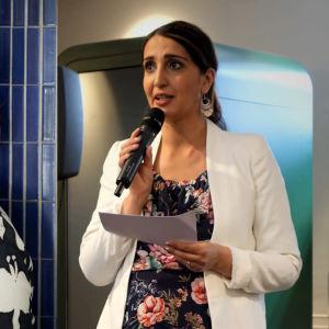 En medelålders kvinna med glasögon och rött hår samt en yngre kvinna som står och pratar i en mikrofon
