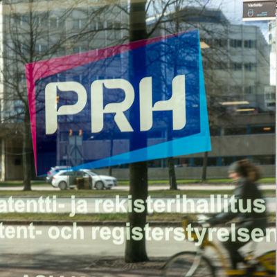 Skylt där det står PRH, Patent- och registerstyrelsen samt en trädörr i ett stenhus.
