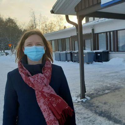 Två vinterklädda kvinnor med munskydd står utanför ingången till hälsovårdscentralen.
