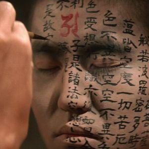 Munkin kasvoja koristellaan japanilaisella kirjoituksella. Kuva elokuvasta Kwaidan.