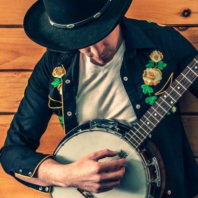 Mies soittaa banjoa, pää kumartuneena alaspäin.