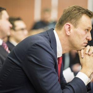 Aleksei Navalnyi istuu keskusvaalilautakunnassa nojaten leukaansa käsiinsä.