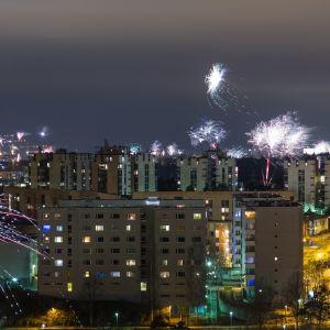 Ilotulitus Helsingissä 1.1.2018. Kerrostalojen ympärillä paukutetaan monia, monia raketteja tummaa taivasta vasten.