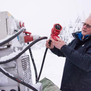 Esa Kemppainen puhdistaa aggregaattia lumesta.