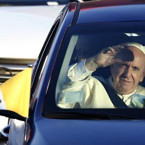 Paavi vilkuttaa paavimobiilinsa ikkunasta.