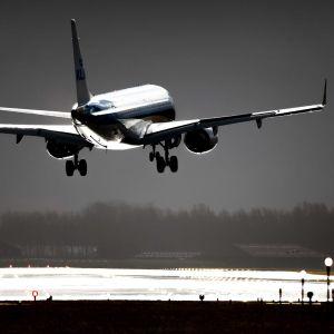 Lentokone nousee Schipholin kentältä, ympärillä kentän valoja ja kiitotien märkä asvaltti.