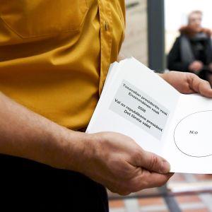 Vaalivirkailija odotteli äänestäjiä tyhjien äänestyslipukkeiden kanssa.