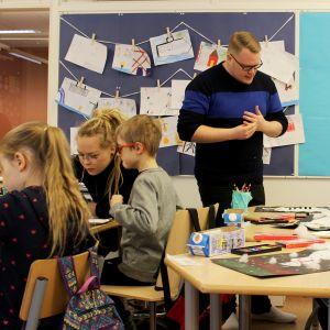 Oppilaat näyttävät askartelutöitään opettajalle